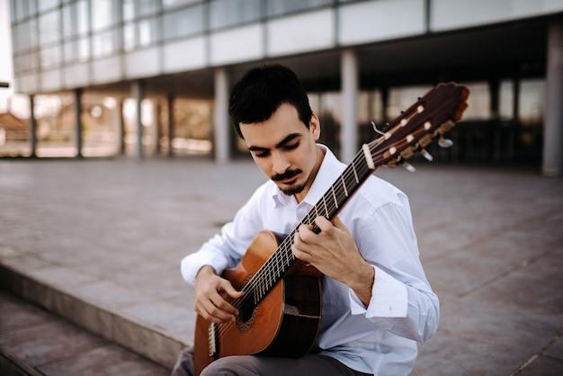 Hübscher junger musiker, der klassische gitarre in der stadt spielt.