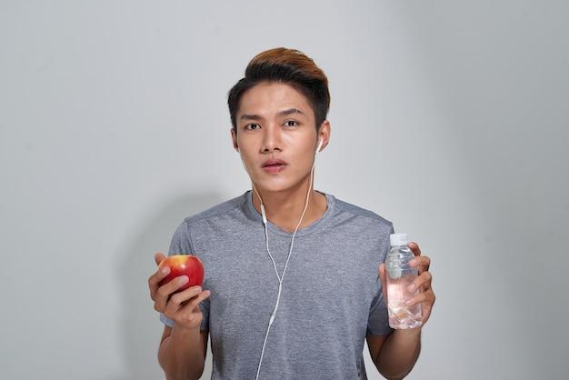 Hübscher junger muskulöser sportler, der eine flasche wasser hält und musik hört