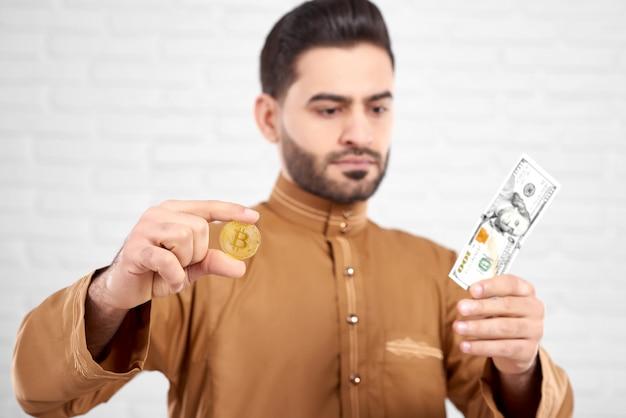 Hübscher junger muslimischer mann, der hundert dollar betrachtet, während er goldenes bitcoin in seinen händen hält