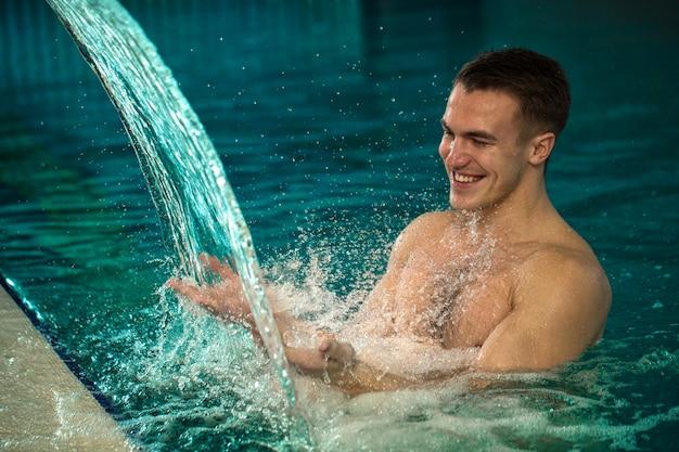 Hübscher junger netter mann, der hydrotherapie am badekurortpool genießt