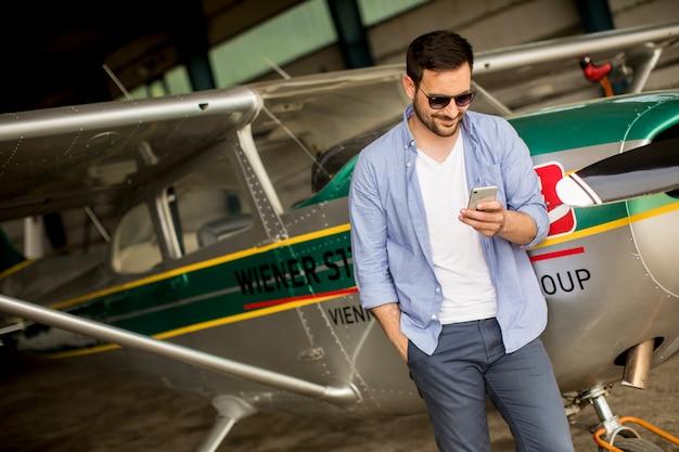 Hübscher junger pilot, der flugzeug im hangar überprüft und handy verwendet