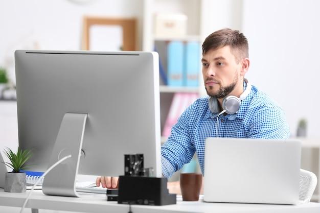Hübscher junger programmierer, der im büro arbeitet