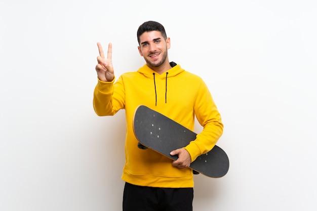 Hübscher junger schlittschuhläufermann über lokalisierter weißer wand lächelnd und siegeszeichen zeigend