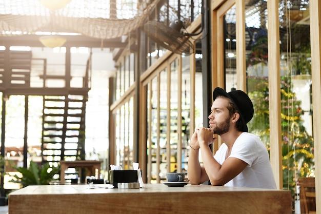 Hübscher junger schriftsteller mit dickem bart, der schwarzen hut trägt, der nachdenklich und in seinen gedanken versunken aussieht