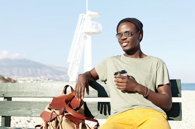 Hübscher junger schwarzer europäischer männlicher reisender gekleidet in der trendigen kleidung, die einige minuten ruhe auf bank hat, tee oder kaffee aus pappbecher während des langen spaziergangs durch den ferienort tagsüber trinkt