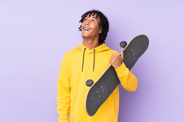 Hübscher junger skatermann über isolierter wand, die beim lächeln nach oben schaut