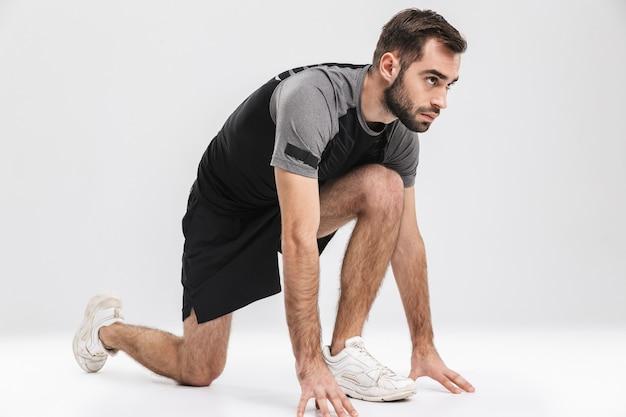 Hübscher junger sport-fitness-mann-läufer posiert isoliert