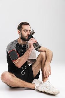 Hübscher junger sport-fitness-mann posiert, hört musik mit kopfhörern, die wasser trinken.