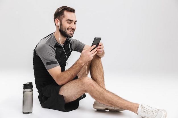 Hübscher junger sport-fitness-mann posiert, hört musik mit kopfhörern mit handy.