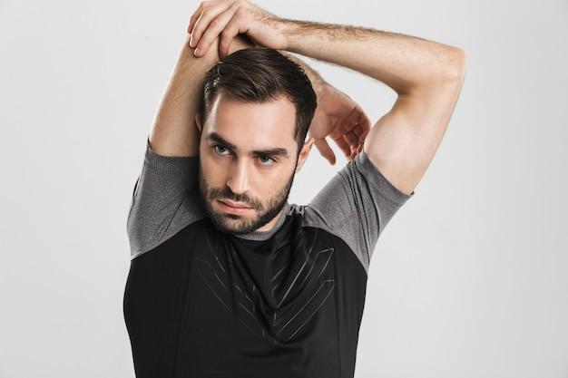 Hübscher junger sport-fitness-mann posiert, macht dehnübungen.