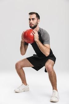 Hübscher junger sport-fitness-mann posiert, macht übungen mit ball.
