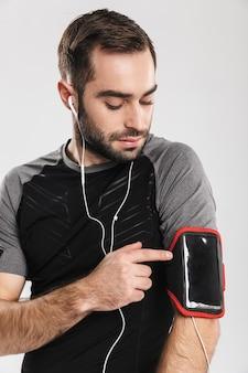Hübscher junger sport-fitness-mann posiert und hört musik mit kopfhörern.