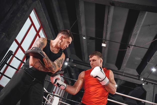 Hübscher junger sportler in boxhandschuhen, die aufwärtshaken stanzen. muskelboxertraining auf boxpfoten mit partner im black boxing gym