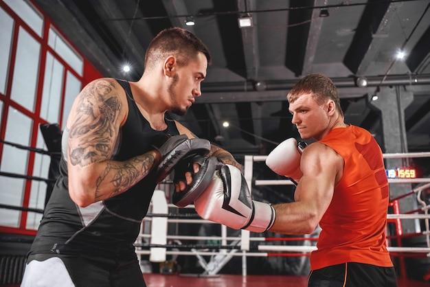 Hübscher junger sportler in boxhandschuhen, die haken stanzen. muskelboxertraining auf boxpfoten mit partner im black boxing gym