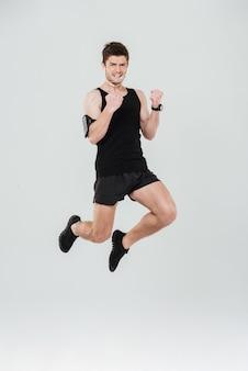 Hübscher junger sportler springend, der siegergeste zeigt