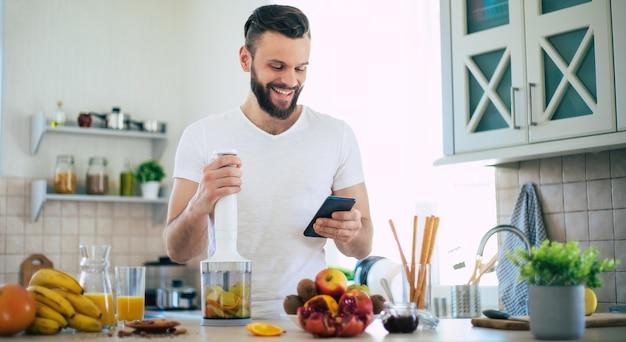 Hübscher junger sportlicher lächelnder mann in der küche bereitet einen smoothie vor