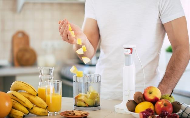 Hübscher junger sportlicher lächelnder mann in der küche bereitet veganen gesunden obstsalat und smoothie in einer guten stimmung zu