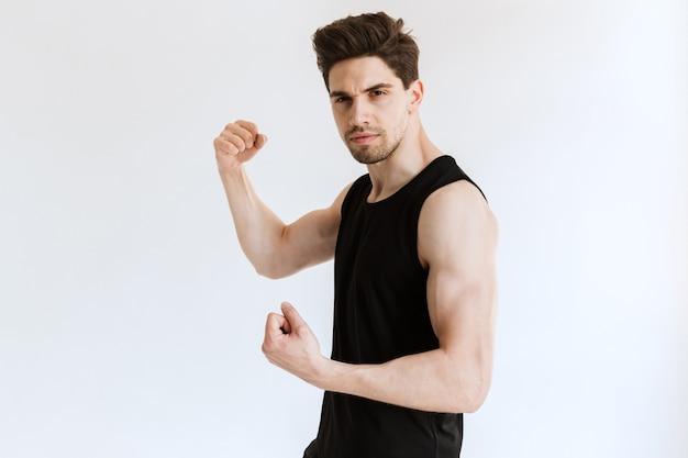 Hübscher junger starker sportler, der bizeps posiert und zeigt.