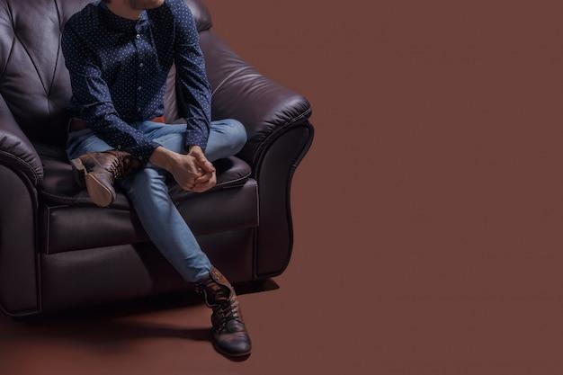 Hübscher junger stilvoller mann, der im lehnsessel hält hände umklammert sitzt.