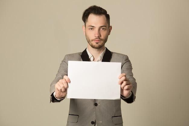 Hübscher junger stilvoller mann in einer jacke, die ein zeichen in seinen händen hält