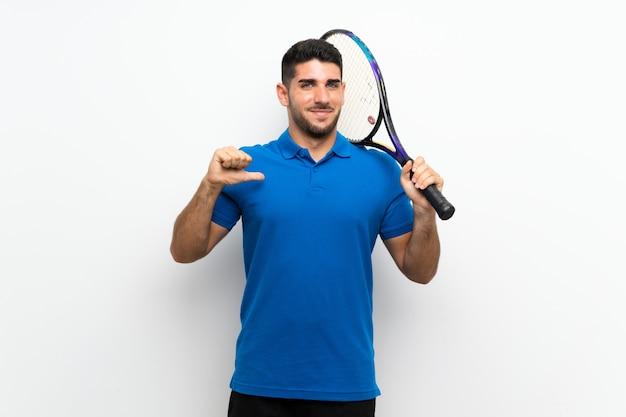 Hübscher junger tennisspielermann auf der weißen wand stolz und selbstzufrieden