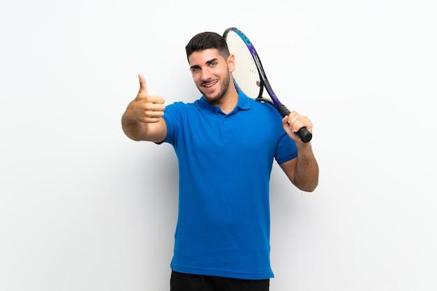 Hübscher junger tennisspielermann auf weißer wand mit den daumen oben, weil etwas gutes geschehen ist