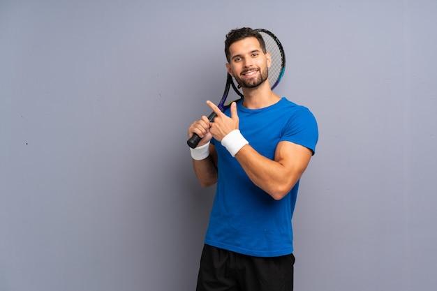 Hübscher junger tennisspielermann, der auf die seite zeigt, um ein produkt darzustellen