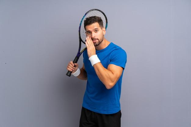 Hübscher junger tennisspielermann, der etwas flüstert