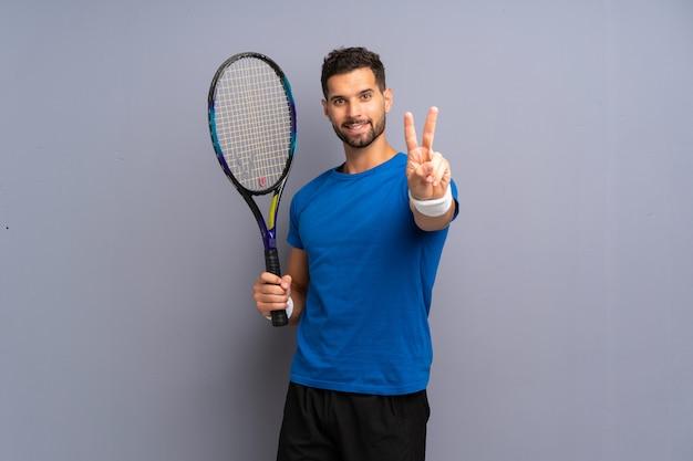 Hübscher junger tennisspielermann, der siegeszeichen lächelt und zeigt