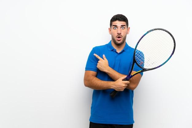 Hübscher junger tennisspielermann über lokalisierter weißer wand überrascht und seite zeigend
