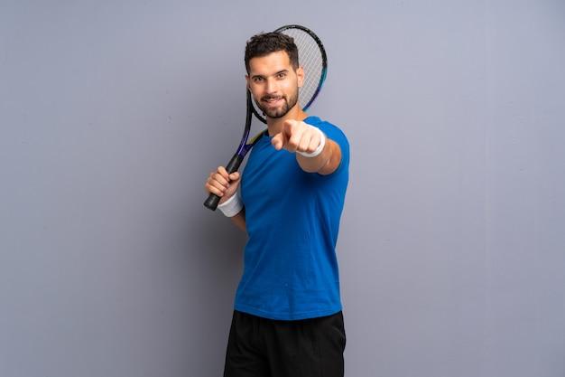 Hübscher junger tennisspielermann zeigt finger auf sie mit einem überzeugten ausdruck
