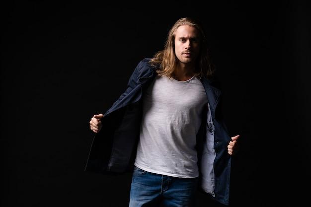 Hübscher junger und fitter mann, der in freizeitkleidung posiert und jacke trägt.