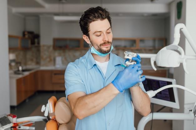 Hübscher junger zahnarzt im weißen kittel hält plastiklayot, während er in seinem büro steht.