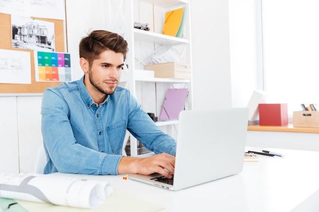 Hübscher junger zufälliger geschäftsmann, der mit laptop arbeitet und am tisch im büro sitzt