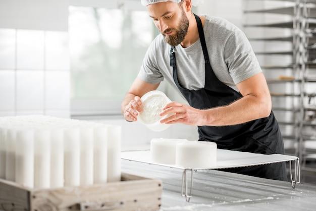 Hübscher käser in uniform, der auf dem kleinen produzierenden bauernhof käse zu formen formt