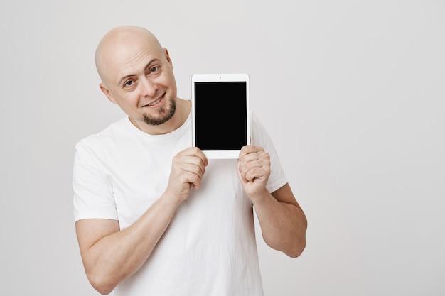Hübscher kahler mann, der digitalen tablettbildschirm zeigt, erfreut erfreut