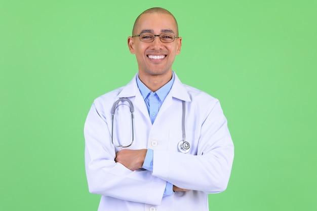 Hübscher kahler multiethnischer mannarzt gegen grüne wand