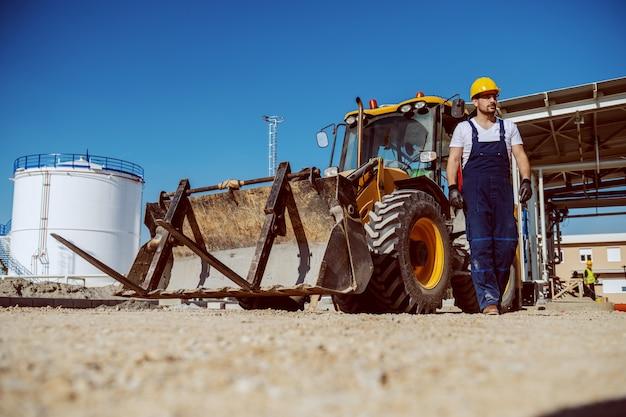 Hübscher kaukasischer arbeiter im overall und im helm auf kopf, die draußen gehen. im hintergrund ist bagger und tank.