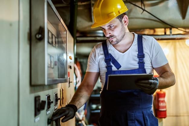 Hübscher kaukasischer arbeiter in overalls und mit helm auf kopf, der innerhalb des schiffes neben armaturenbrett steht, knopf drückt und tablette verwendet.
