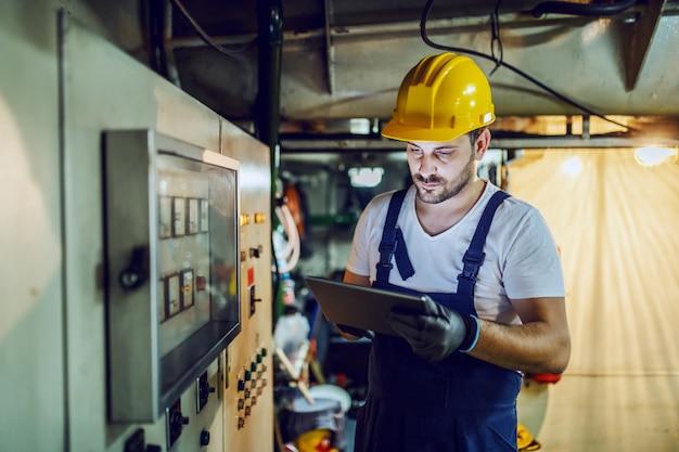 Hübscher kaukasischer arbeiter in overalls und mit helm auf kopf, der innerhalb des schiffes neben armaturenbrett steht und tablette verwendet.