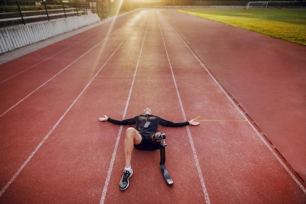 Hübscher kaukasischer behinderter junger sportlicher mann, gekleidet in sportbekleidung und mit künstlichem bein, das auf rennstrecke liegt und musik über smartphone hört.