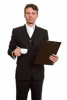 Hübscher kaukasischer geschäftsmann, der klemmbrett und kaffeetasse hält