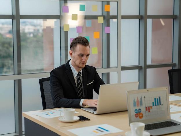 Hübscher kaukasischer geschäftsmann im anzug, der mit laptop im büro mit glücklichem ausdruck arbeitet. tablet-computer mit grafiken, diagrammen und diagrammen auf dem bildschirm. finanzanalyse.
