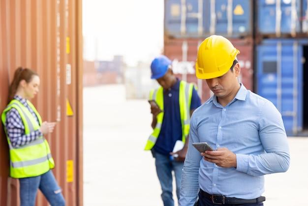Hübscher kaukasischer ingenieur und gruppenarbeiter, der auf digitalem mobiltelefon in einer pausenzeit steht, die mit frachtcontainer im hintergrund steht