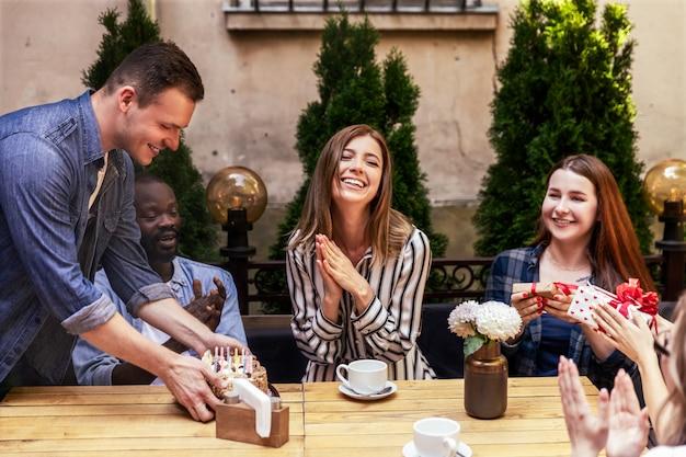 Hübscher kaukasischer junge holt geburtstagskuchen für eine feierparty