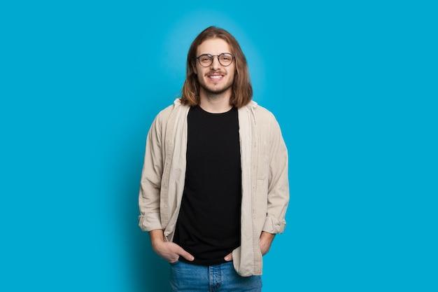 Hübscher kaukasischer junge mit langen haaren und bart hält hände in seinen taschen, während er an einer blauen wand jubelt