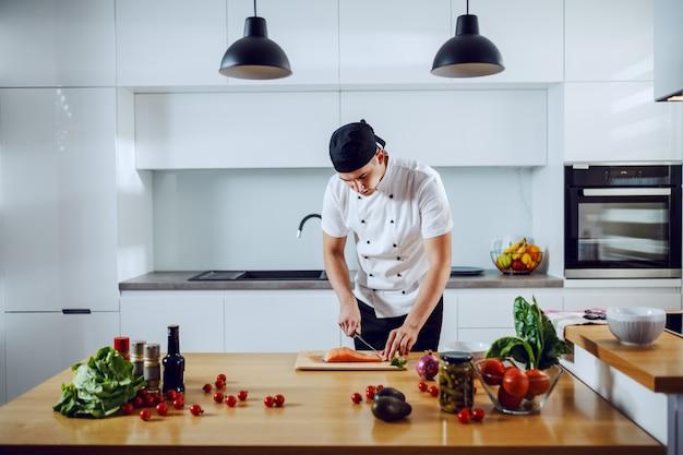 Hübscher kaukasischer kreativer koch, der in der küche steht und lachs für das mittagessen schneidet
