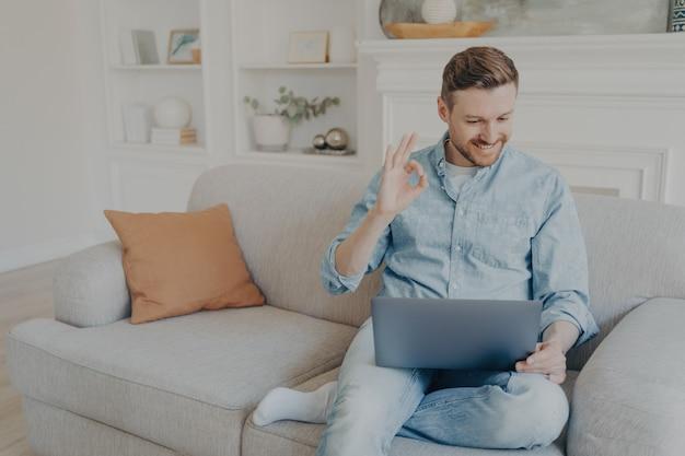 Hübscher kaukasischer männlicher freiberufler lächelt und zeigt zeichen ok mit den fingern während einer videokonferenz auf dem notebook, junger mann in freizeitkleidung mit drahtlosem laptop für online-meeting von zu hause aus