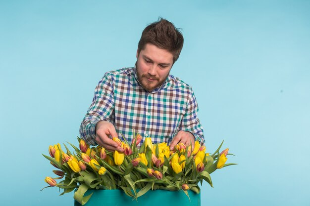 Hübscher kaukasischer männlicher gärtner, der einen blumenstrauß von tulpen im blauen studio macht.