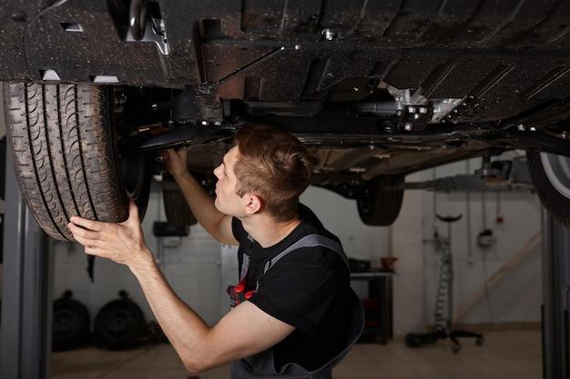 Hübscher kaukasischer mann, der boden des autos repariert
